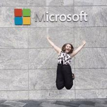 A woman leaps into the air before a gray wall emblazoned with the Microsoft logo.