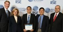 A group of men and a woman holding an award certificate as they stand before a wall with IISE written on it.