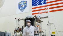 A man in a white cleanroom suit stands in front of a spacecraft under construction, pointing backwards at it. On the wall in the background are a sign for the OSIRIS-REx mission and a large U.S. flag.
