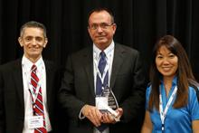 Scott Miller, Larry Head and Jamie Blakeman on stage as Head receives his ITS Arizona Member of the Year Award