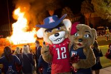 Wilbur and Wilma Wildcat posing for the camera in front of a bonfire