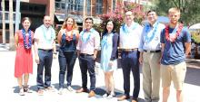 Eight new engineering faculty members stand in the AME courtyard wearing festive leis.