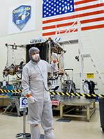 Bradley Williams with the OSIRIS-REx spacecraft in the Lockheed Martin cleanroom. Photo by Symeon Platts/The University of Arizona.