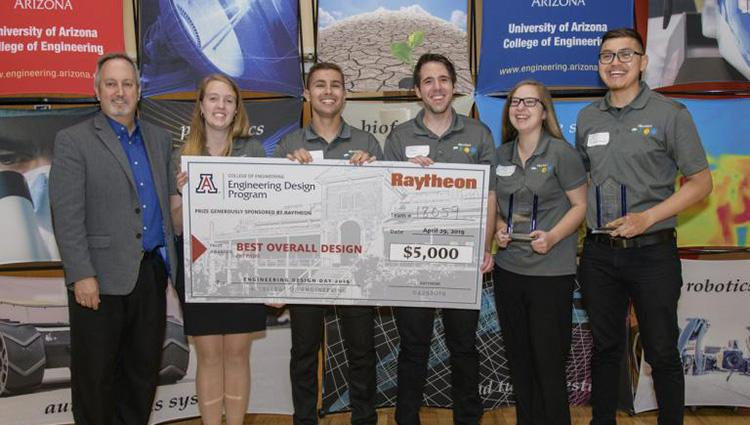 "A group of five students in matching grey polos and a man in a blazer hold up a giant, $5,000 check, made out to ""Best Overall Design."""