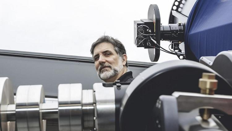 Roberto Furfaro stands next to a telescope