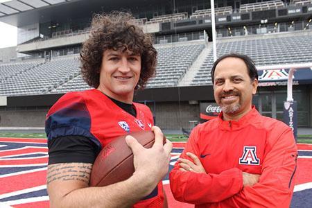 UA linebacker Jason Sweet stands in Arizona Stadium with associate professor Ricardo Valerdi