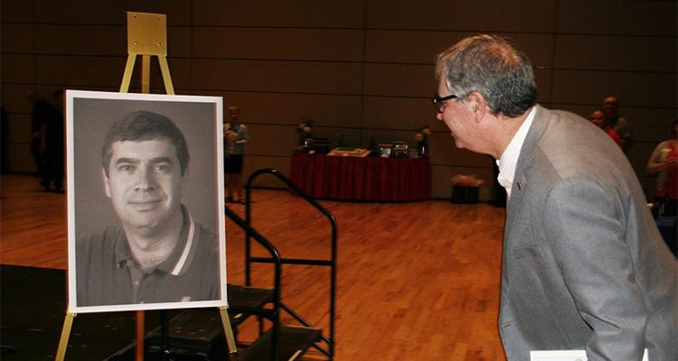 Jeff Goldberg, wearing a gray suit, looks at a 30-year-old portrait of himself on an easel by the