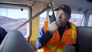 A man wearing an orange safety vest sits inside a van and speaks into a radio handset.