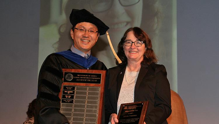A woman in a black suit jacket accepts a plaque from a man wearing graduation regalia. He is also holding a larger plaque with four names inscribed.