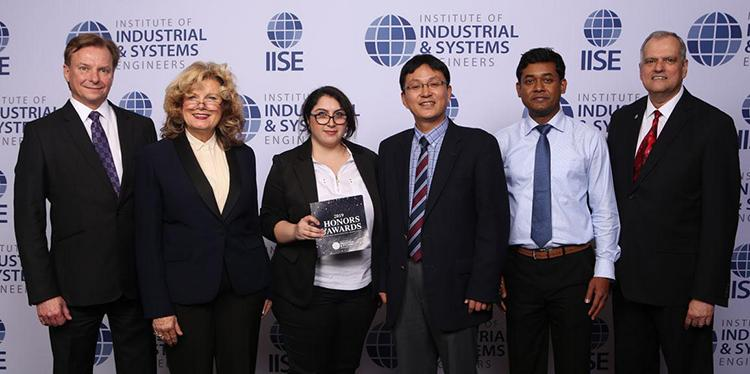 Six people in suits stand in front of an IISE backboard