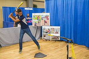 Swing, batter! At the Science of Baseball booth at STEAMworks 2016. Photo courtesy of the UA Office of the Chief Information Officer.
