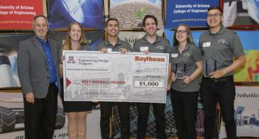 """A group of five students in matching grey polos and a man in a blazer hold up a giant, $5,000 check, made out to """"Best Overall Design."""""""